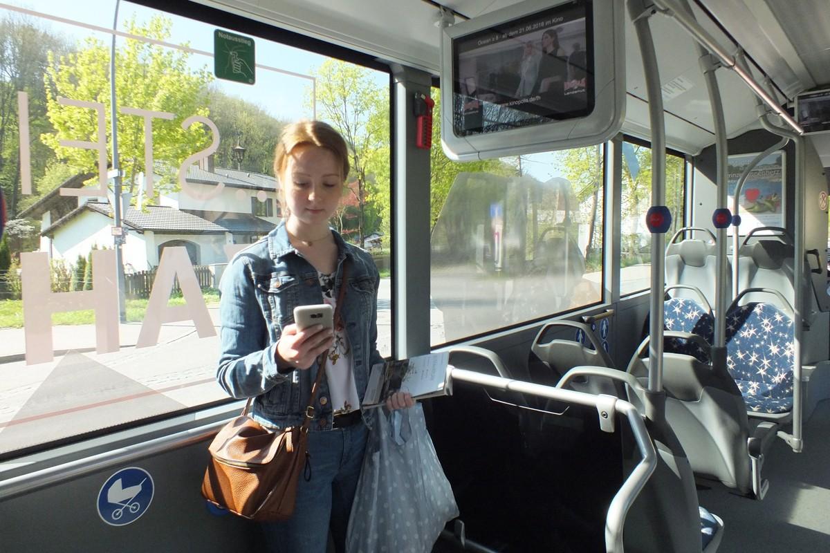 Junge Frau mit Jobticket im Bus