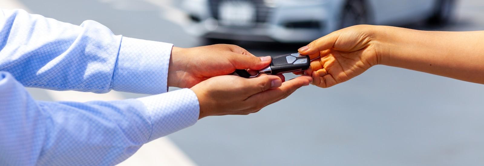 Übergabe eines Schlüssels für ein Carsharing-Fahrzeug in Landshut