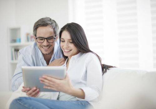 Paar sieht sich zuhause auf dem Tablet interaktive Rechnungserläuterung an