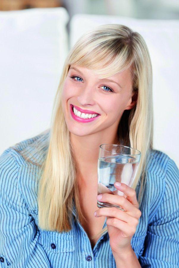 Frau mit Wasserglas in der Hand